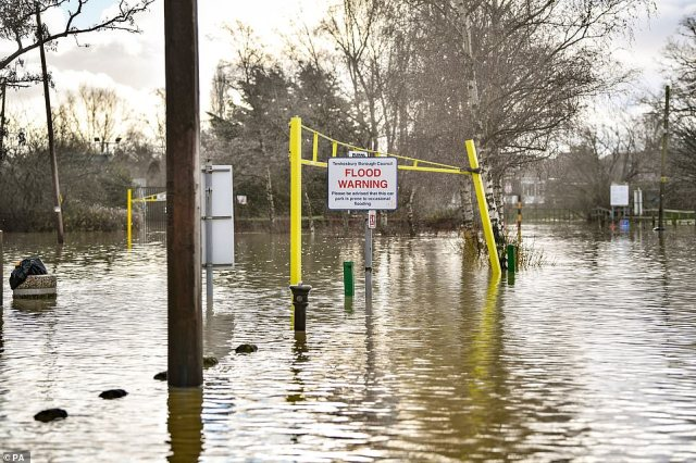 A flood warning sign at the entrance to a flooded car park beside Tewkesbury Abbey,Gloucestershire, where flood watches are in place with more wet weather expected in the coming days