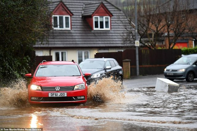 Cars make their way through floodwater and past floating debris after heavy rain in Cardiff South Wales