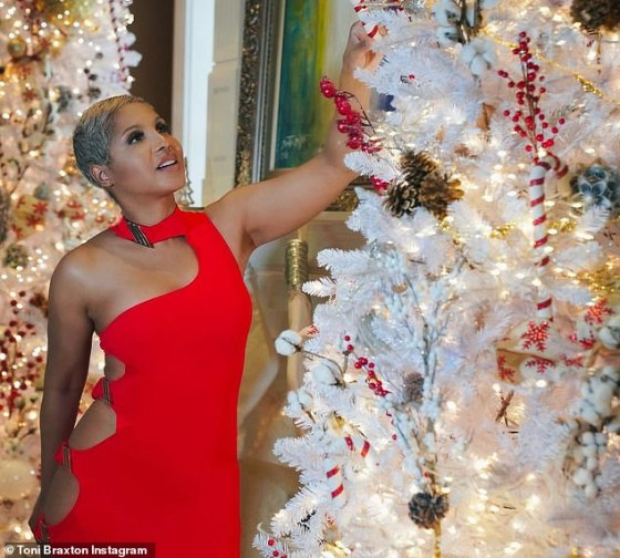 Red-Christmas: Toni Braxton (53) chirps in a red dress with side necklines as she decorates her tree on Christmas Eve