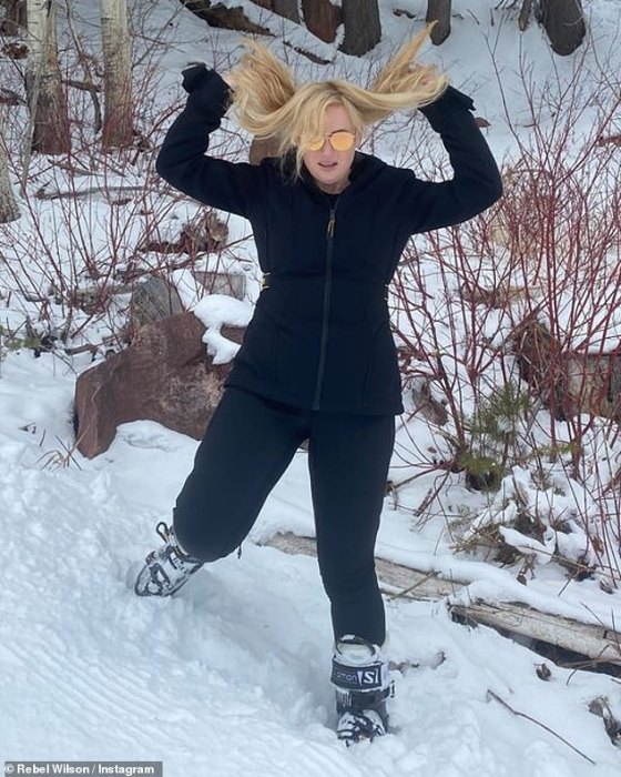 Rollover: The Pitch Perfect star happily posed for pictures in the snow, flipping over her wavy blue dresses at one point