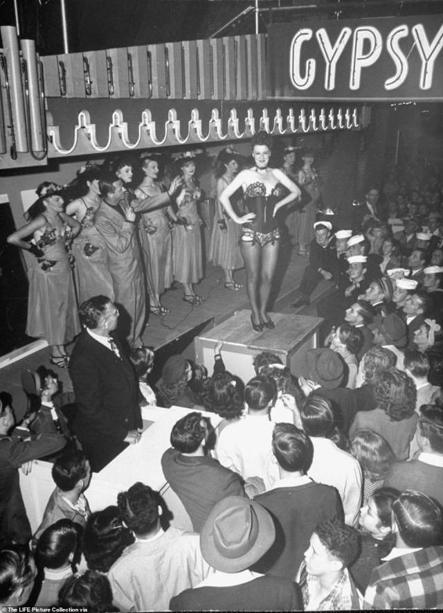 Gypsy Rose Lee told bawdy jokes with sharp comedic timing. Above, she laughs and soaks up cheers from the crowd  imploring her to 'take it off.' The New York Times wrote: 'she eschewed the traditional crudities of burlesque. The burlesque entertainer was world-famous for her act, that included