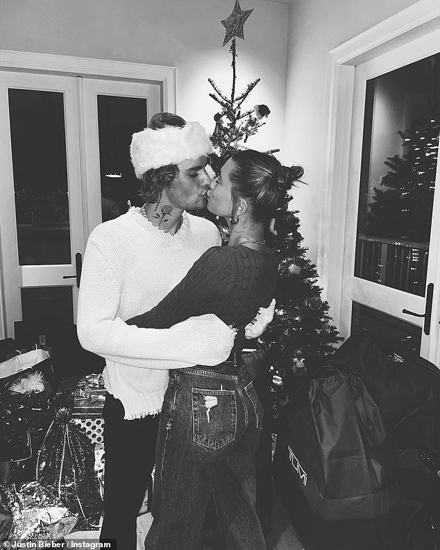 Justin Bieber smooches wife Hailey and breaks out into dance with friends by the Christmas tree