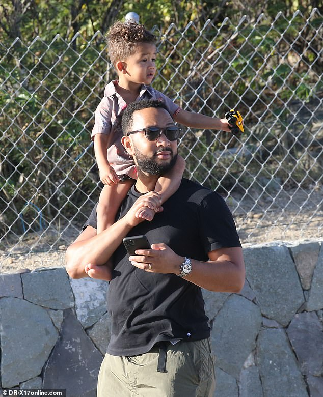 Too cute:Adorable little Miles sat atop his father's shoulders