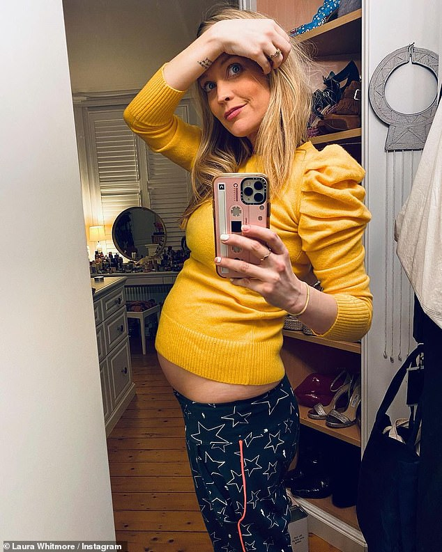 Blooming lovely:Laura Whitmore looked every inch the proud mum-to-be as she showcased her growing baby bump in a bright yellow jumper as she posed for a sweet Boxing Day snap