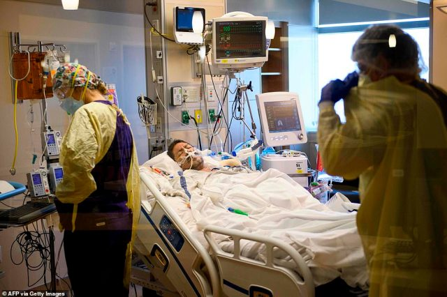 An intubated patient lies on a bed after being turned from laying on their stomach in the COVID-19 intensive care unit at Renown Regional Medical Center in Reno, Nevada, on December 16