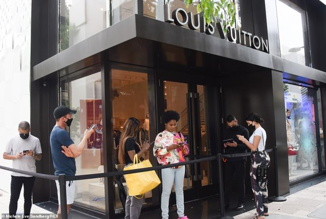 Shoppers are seen above standing in line outside Louis Vuitton on Christmas Even in Miami's Design District