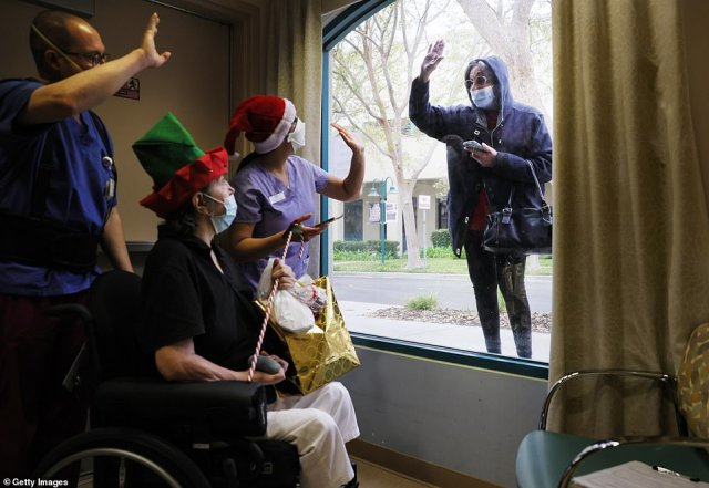 Juliet Babayan (right) waves goodbye to her sister Violet Bonyad (seated) and caregivers after bringing a present for Violet and visiting through a window at the Ararat Nursing Facility on Christmas Eve in Mission Hills, California