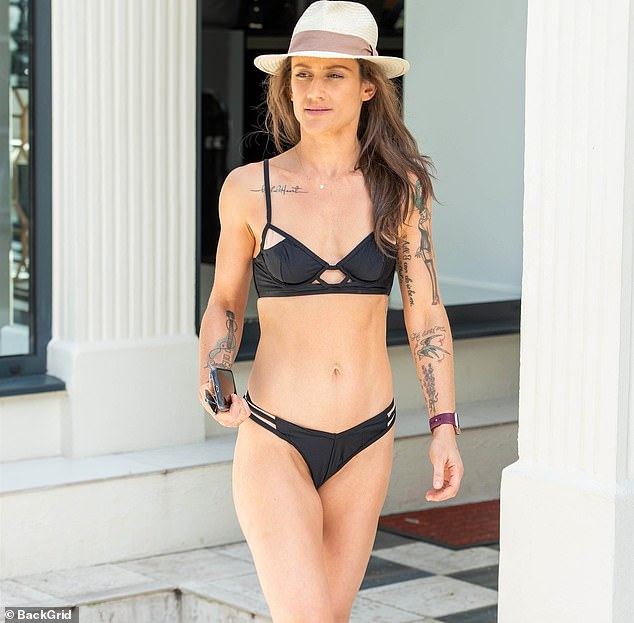 Katie Waissel shows off her taut figure in an intricate black cut-out bikini
