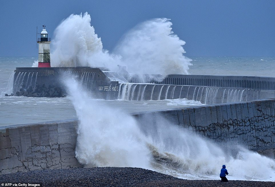Waves crash over Newhaven Lighthouse and harbour wall on the south coast of England as Storm Bella rages on this morning