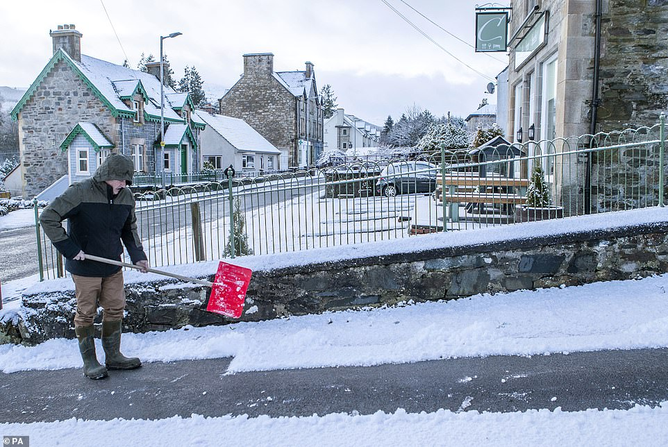 The Met Office has issued a snow warnings for parts of Scotland. Pictured: A man clears snow from a driveway in Stirlingshire
