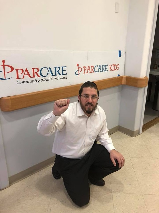 Schlesinger pictured raising a fist in front of a ParCare sign