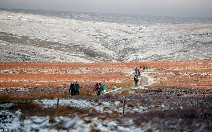 Hikers in light snow walk through Hope Woodlands Moor in the Peak district of Derbyshire, after days of wintry weather