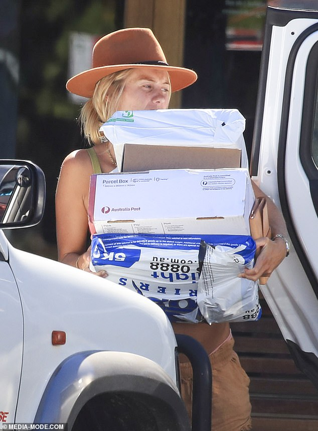 Struggles: Tough gig: After making her way to the car, Elyse was seen grimacing in frustration as she attempted to open the car boot and load the parcels inside