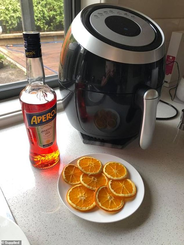 The woman said she heats thinly-sliced slices of orange in her device at 100 degrees Celsius for half an hour to dehydrate them and uses them as decoration for her glass (pictured)