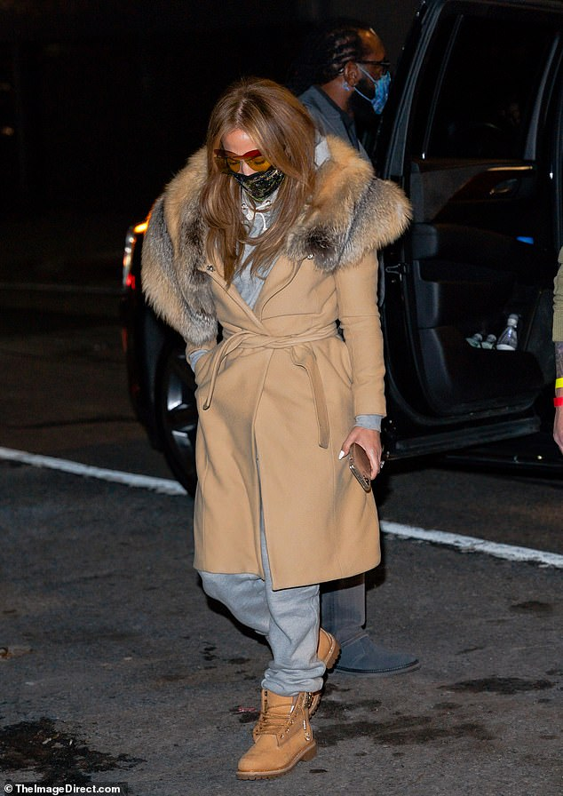 Head down: The singer and actress, 51, wore a fur-trimmed camel wrap coat, which was belted at the waist with a matching sash