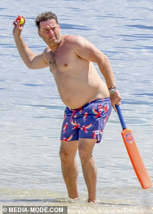 Batter up! Removing his shirt for the occasion, Karl was seen clutching a waterproof cricket bat as he stood ankle-deep in the shallows