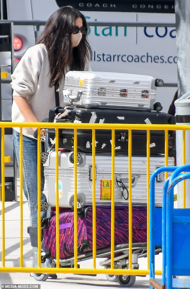 Into quarantine: Wearing a nude-coloured face mask, Jessica wheeled a trolley piled high with luggage as she made her way outside to a waiting bus