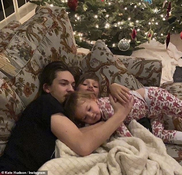 Snuggle fest: It comes after she spread some holiday cheer with a photo of her three children snuggling in front of another Christmas tree