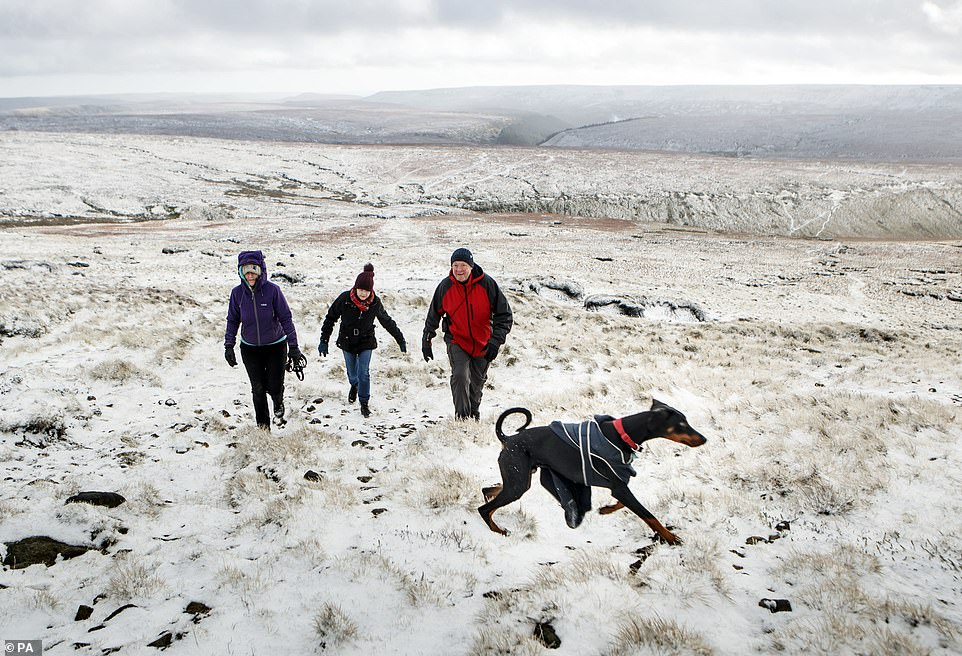 Hikers in snow on Bleaklow Moor in the Peak district of Derbyshire, after days of wet and wintry weather across the Christmas break, with a cold snap and icy conditions still to come