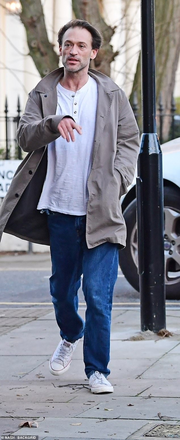 Casual: Paul, 41, wore a baggy white top over jeans, wrapping up in a stone winter coat
