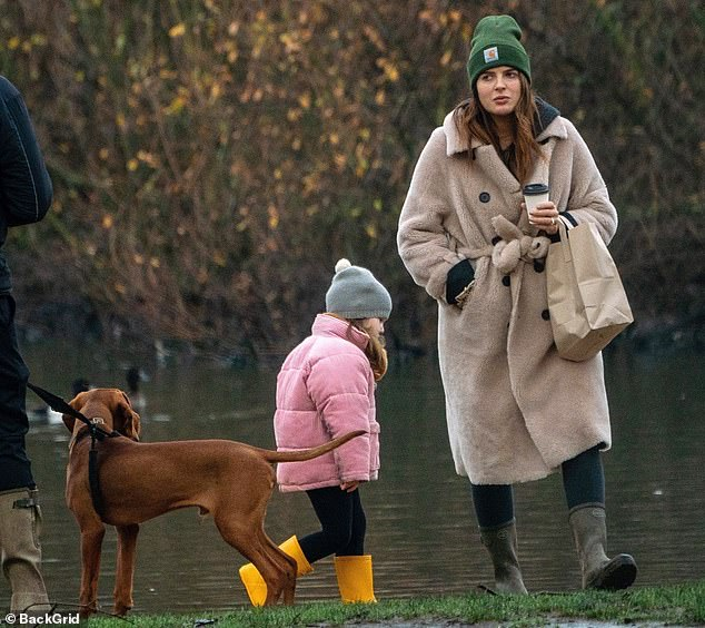 Well wrapped:With temperatures plummeting the expectant mum stayed warm beneath a thick belted winter coat as the family took their pet dog Pedro to a local park