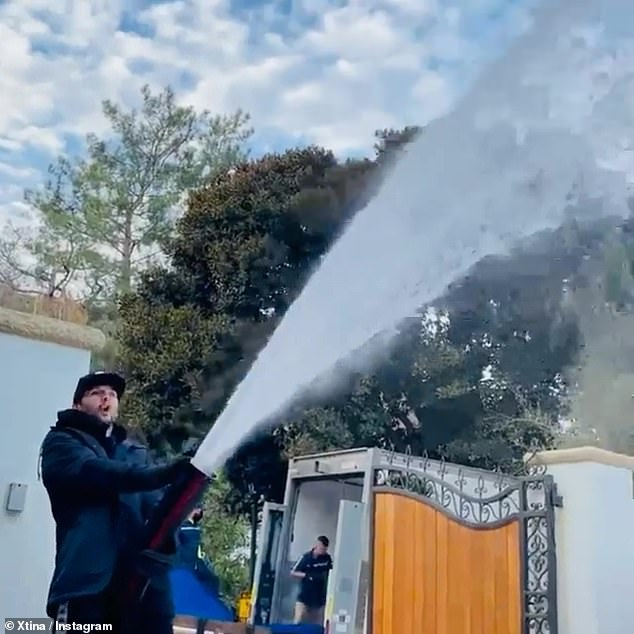 Let it snow: The Burlesque star posted a video of a man hosing their gated yard down with snow, for a white Christmas in Beverly Hills, complete with a bounce house