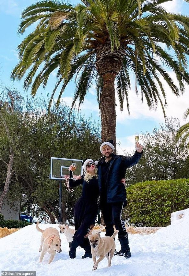 White Christmas: He and Rutler picked up a few glasses of champagne as they took a picture on their freshly powdered lawn, matching a black Santa hat