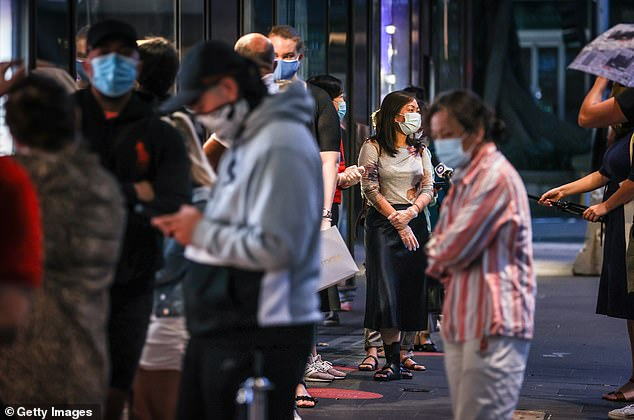 Shoppers wearing face masks stand in a line as they wait to enter the David Jones store during the Boxing Day sales in Sydney