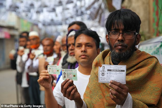 Bangladeshi voters hold up their national ID cards as they wait in line to vote in the Dhaka City Corporation Election on February 1, 2020. A fingerprint is required when applying for the ID card, though the Sarker family were able to obtain cards after showing medical certificates and using other forms of biometric data including retina scans and facial recognition [File photo]