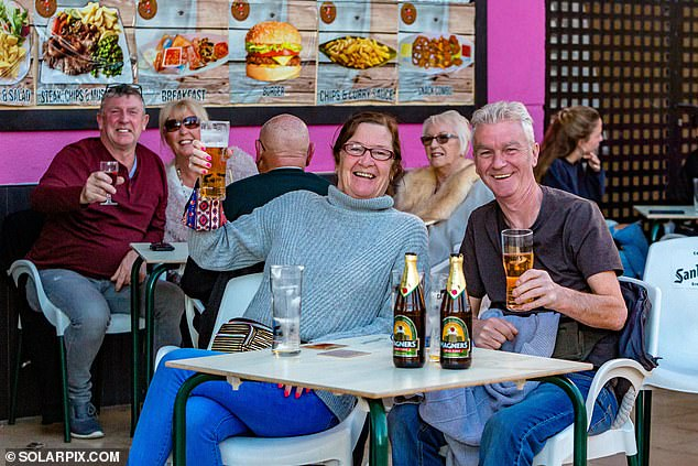 Britons who moved over to Spain for a warmer climate were today pictured enjoying pints inside a cafe amid news the UK could be covered in a blanket of the white stuff this week
