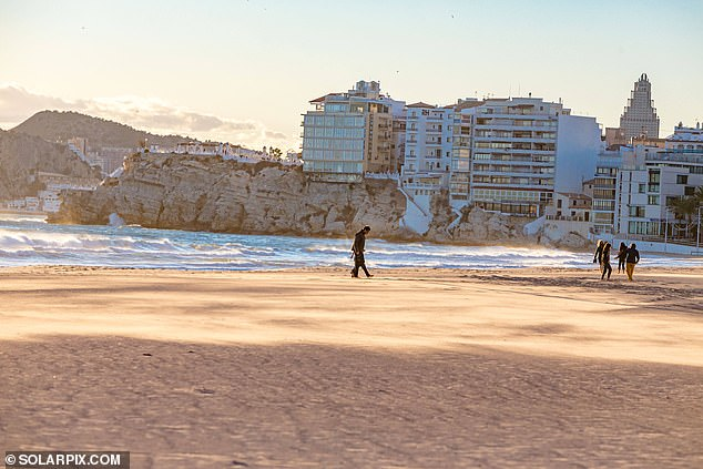 One photograph showed an empty stretch of coastline as a small group of walkers headed along the seafront amid temperatures that are still a little chilly for sunbathing - at 58F (14C)