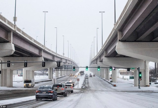 Traffic heads west through the snow on Dodge Street towards 114th Street underneath the West Dodge Expressway in Omaha, Nebraska. Officials are advising motorists stay off the roads