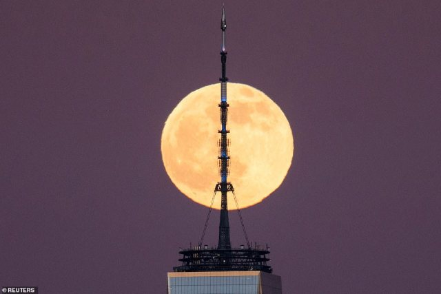The moon is pictured passing by the antenna located at the top of One World Trade Center in New York on Tuesday night