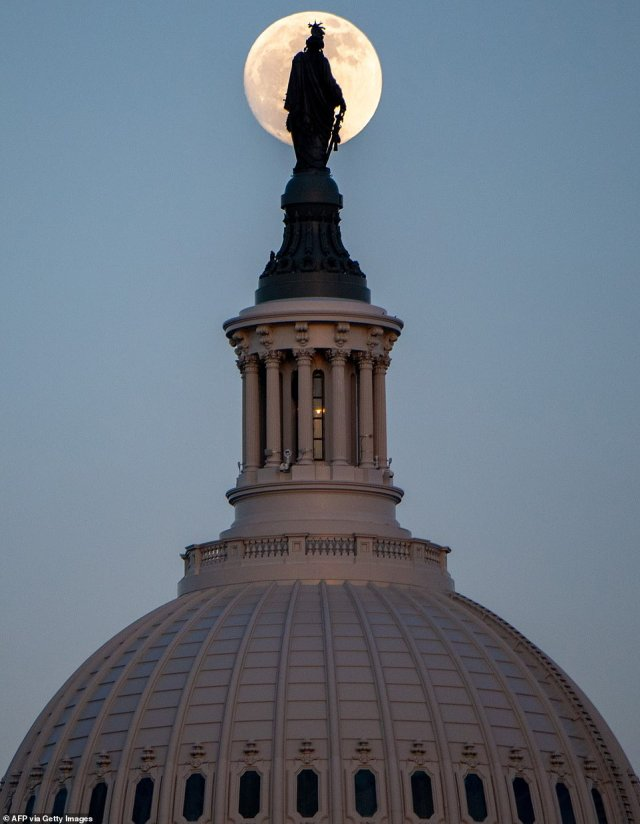 The moon rises over the US Capitol Dome at sunset in the nation's capital, Washington D.C.
