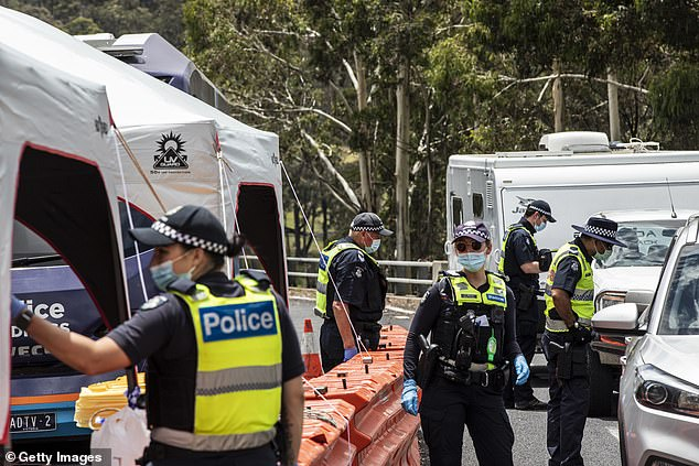 Victorian police are seen patrolling checkpoints in Mallacoota after new border restrictions were imposed on NSW, barring residents of Wollongong and the Blue Mountains