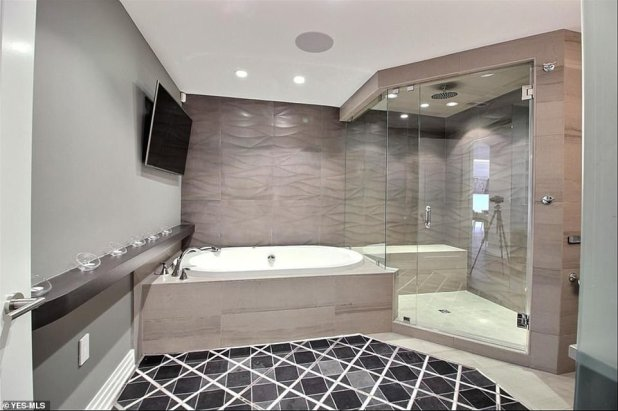 Smooth: Another bathroom has modern tiling and a chic bath for guests