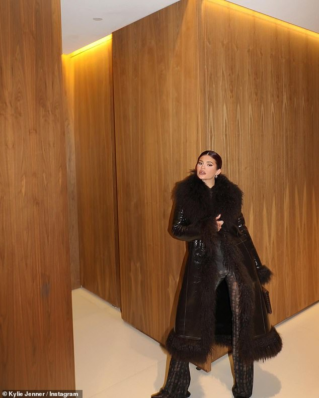 Stylish: Kris looked elegant in a furry black coat with lustrous slate gray pants