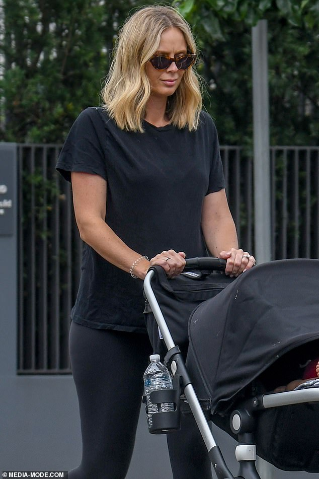 Downtime: The 34-year-old covered up her baby bump in a baggy black T-shirt and doted on her son as they strolled around