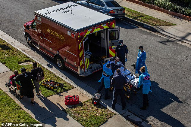 Pictured: A person is loaded into an ambulance after being administered oxygen
