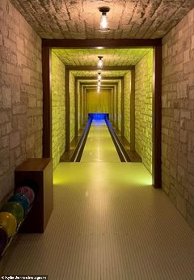 Playing a round: She also showed off the long stone corridor with the bowling alley