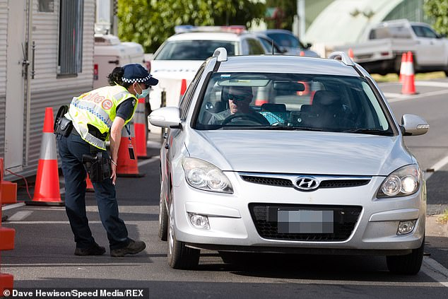 Pictured: Police check permits as Victorian rush to beat the border closures after being given almost no notice to return home during COVID-19 in Victoria on January 1