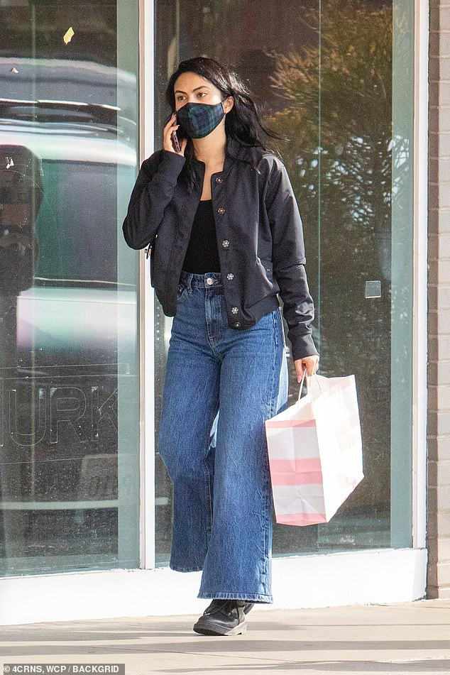 Casually stylish: Riverdale star Camila Mendes ran some errands in LA Sunday wearing a tartan face mask along witha black top tucked into blue jean flares and a black lightweight jacket