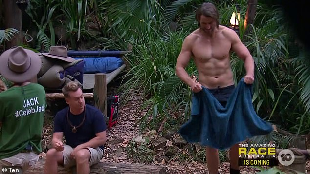 Buff: Ash (right) stripped off his shirt to perform a series of tricep dips in the jungle