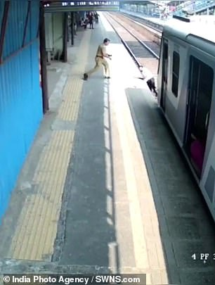 A local police officer, S.B. Nikam, runs towards the man, who is still in the middle of the railway as the train approaches