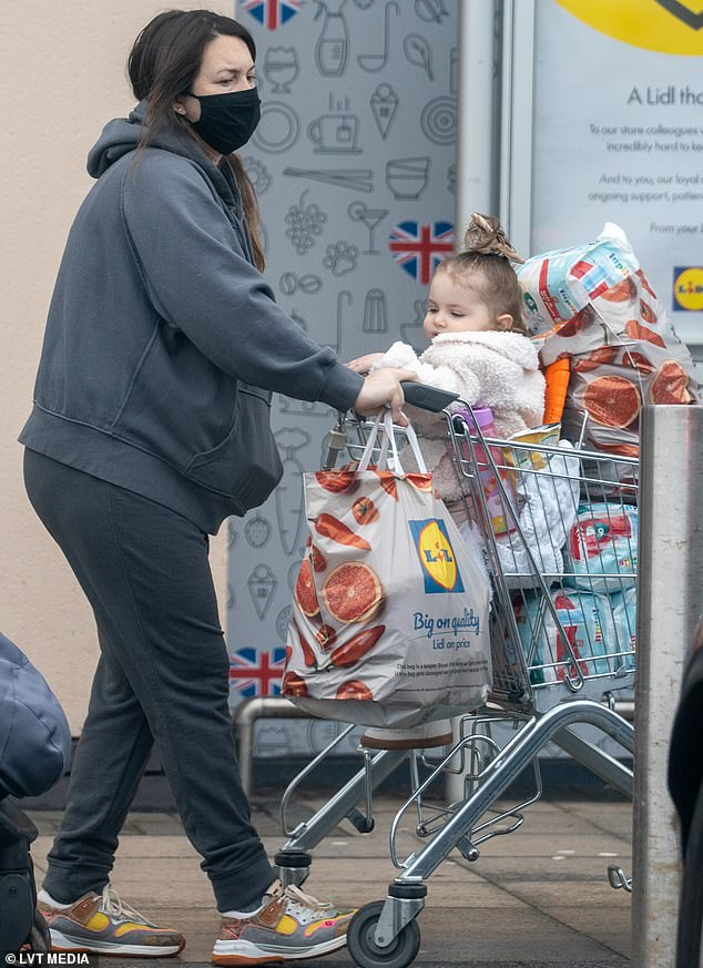 Relaxed outfit: Lacey Turner covered her blossoming baby jump with a hooded jacket on Monday as she went food shopping with her 18-month-old daughter, Dusty