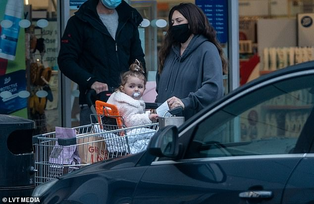 Mother daughter duo: Her only child looked adorable in a pastel pink coat as she sat on a blanket in the shopping trolley