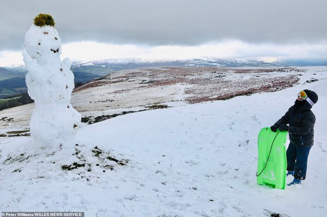 Rhys Williams, eight, looks up at a snowman while sledging in snow and freezing temperatures in the Llangynidr Mountains in the Brecon Beacons, Mid Wales, this morning