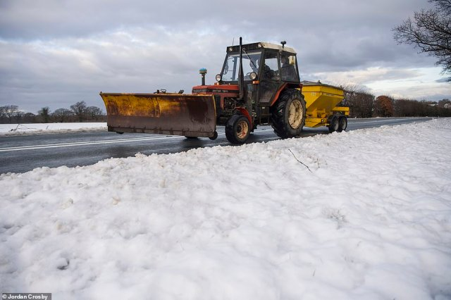 A tractor with a snow field drives by a snowy field after a car left the road near Great Broughton on The North Yorkshire Moors this morning