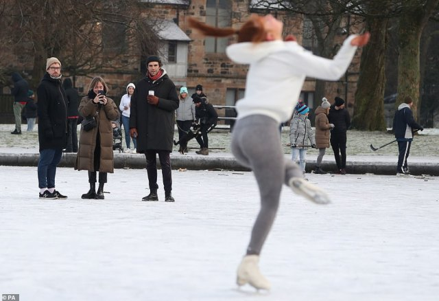 A person ice skates on a frozen pond in Queen's Park in Glasgow as spectators watch
