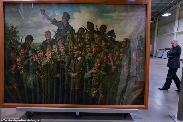"""William Layer of the Army Public Affairs strolls past Emil Schiebe's """"Hitler at the Front,"""" an oil on canvas painting from 1942 that was taken by US soldiers during WWII"""
